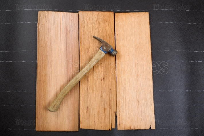 Used roofing hammer with new cedar wood shingles on felt paper