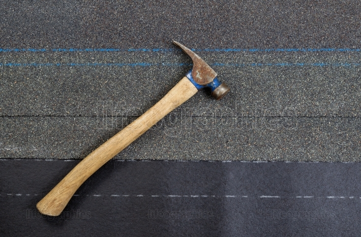Used roofing hammer with new composite shingles on felt paper