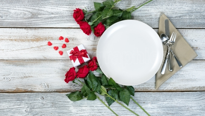 Valentine dinner setting with flowers and gift on white table