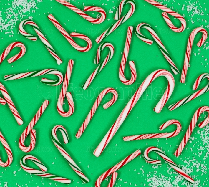 Variety of candy canes on snowy green background