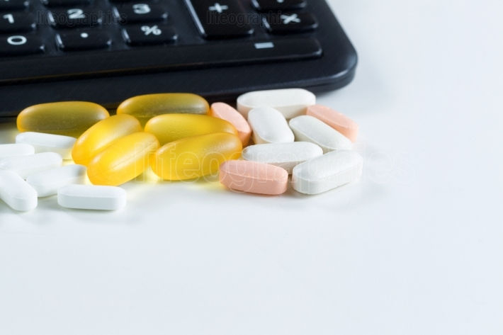 Variety of medication in front of calculator on white