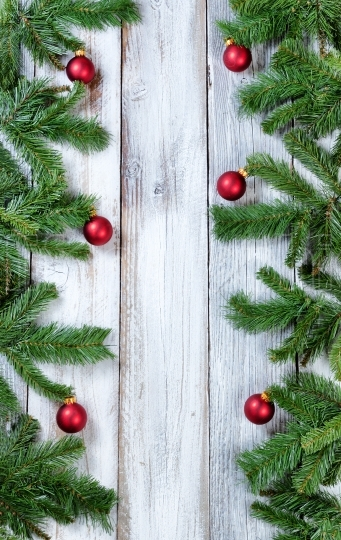 Vertical borders of Christmas red ornaments hanging in evergreen