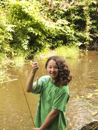 Very happy young girl catches small trout