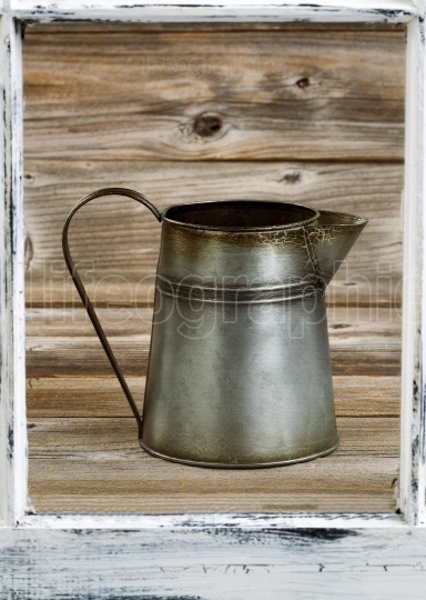 View of vintage coffee pot thru old window on rustic wooden boar