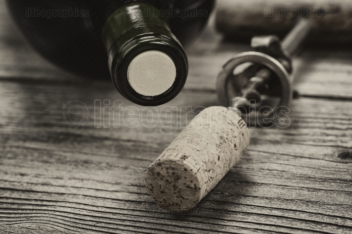 Vintage bottle of wine ready to open on aged wood