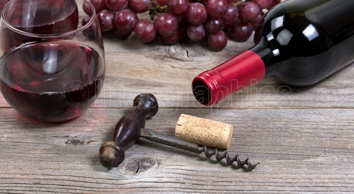 Vintage corkscrew with red wine bottle with grapes and glasses i