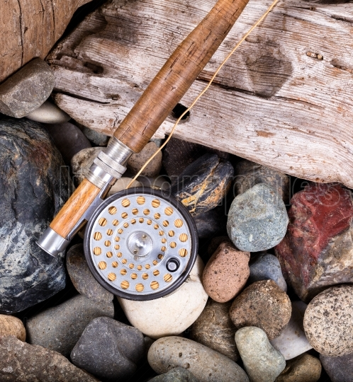 Vintage fly fishing outfit on rocks and wood background