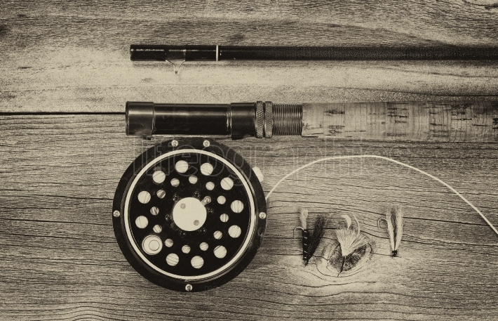 Vintage fly reel and rod on aged wood
