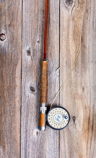 Vintage fly rod and reel on rustic wooden boards