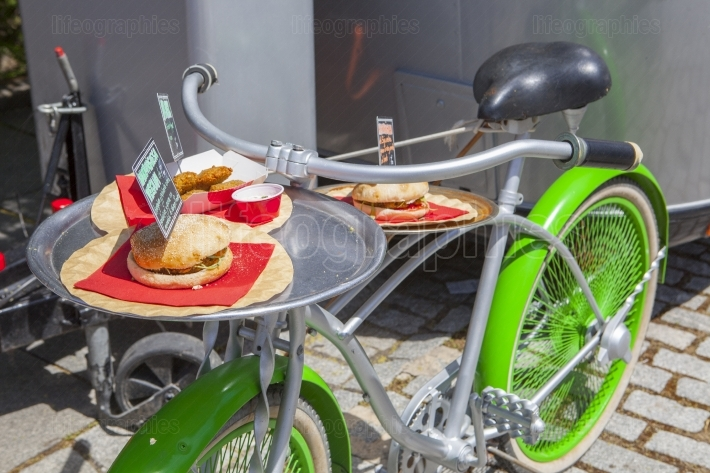 Vintage green bike used for offer meals beside food truck traile