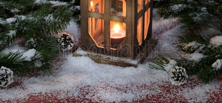 Vintage lantern with burning candle on snowy rustic red wooden b