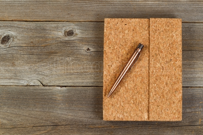 Vintage metal pen and cork covered notepad on rustic wooden desk