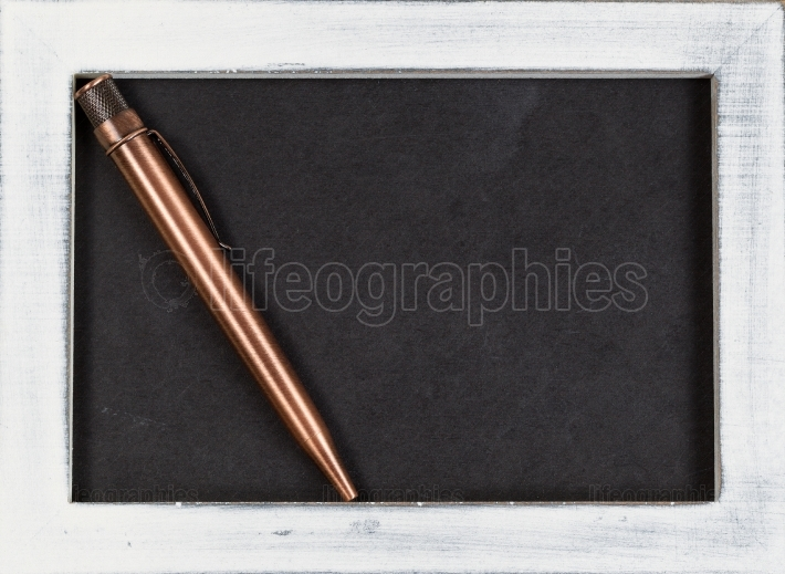 Vintage metal pen on used chalk board