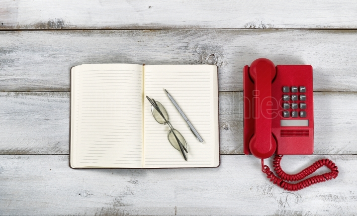 Vintage red phone and notepad with pen and reading glasses on ru