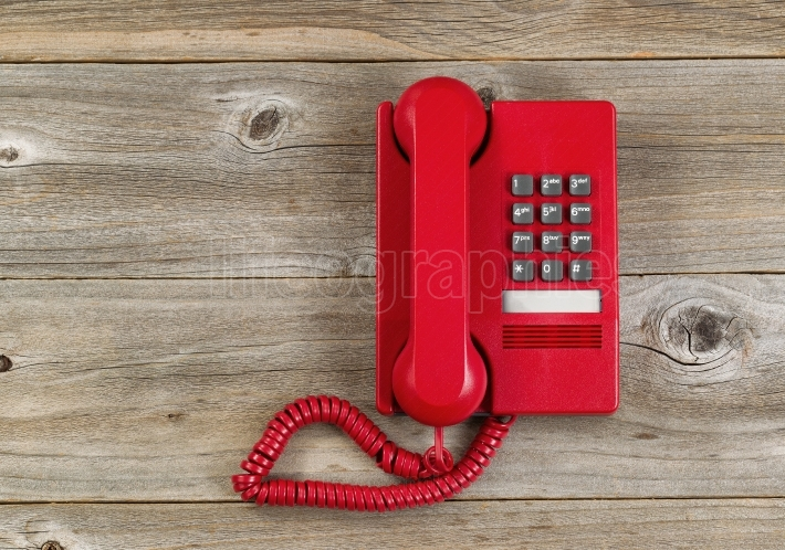 Vintage red phone on rustic wooden boards