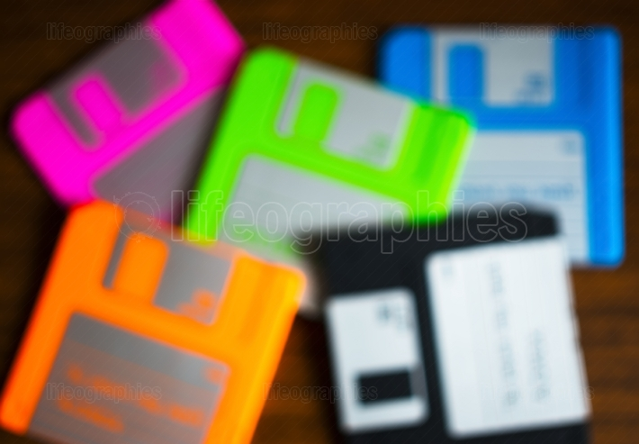 Vintage set of floppy discs on wooden desk bokeh
