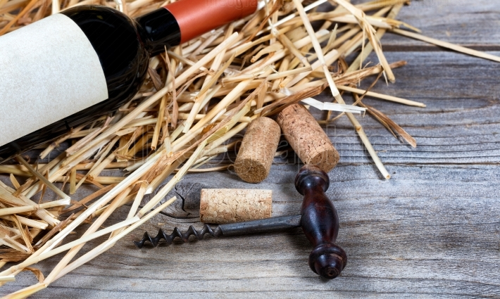 Vintage wine corkscrew with bottle of wine on straw in backgroun