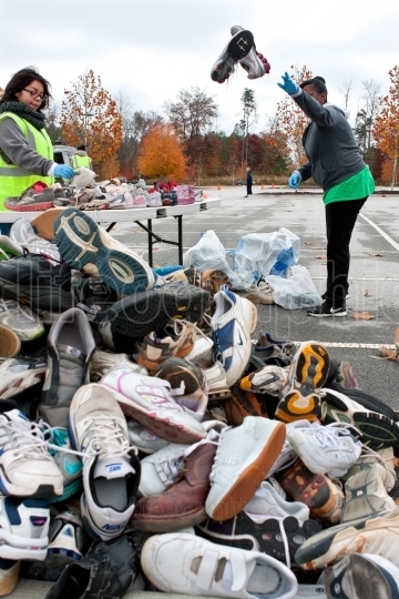 Volunteer Tosses Sneakers Into Shoe Pile At Recycling Event
