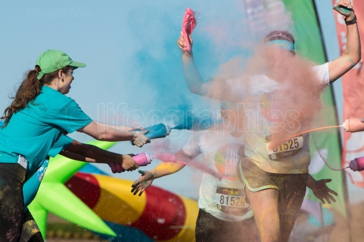 Volunteers douse runners with colored corn starch at color run