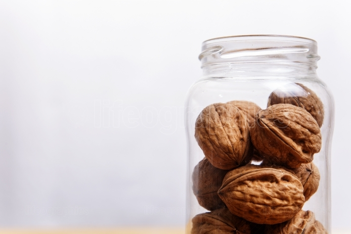 Walnuts on glass jar over wooden surface