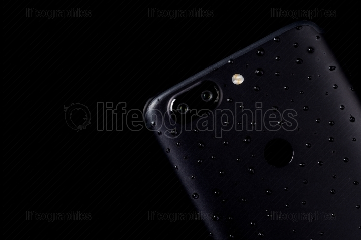 Water drops on black smartphone with dual camera and fingerprint