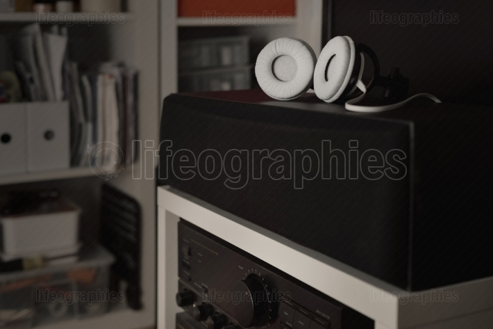 White headphones over central speakers from a 7.1 thx hi-fi sound system
