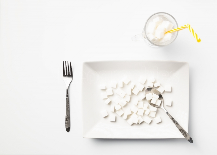 White plate and glass cup with sugar cubes  Concept of unhealthy