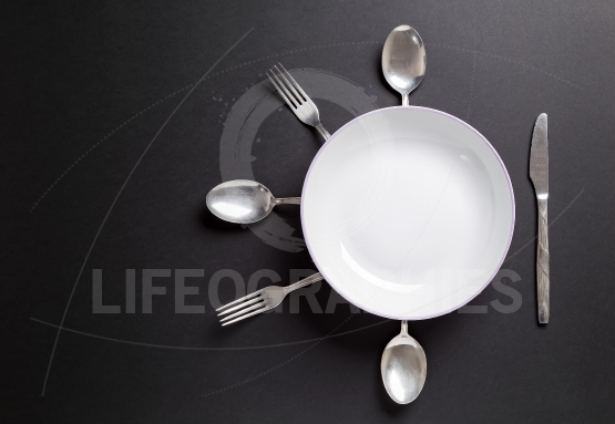 White plate with cutlery over black background.