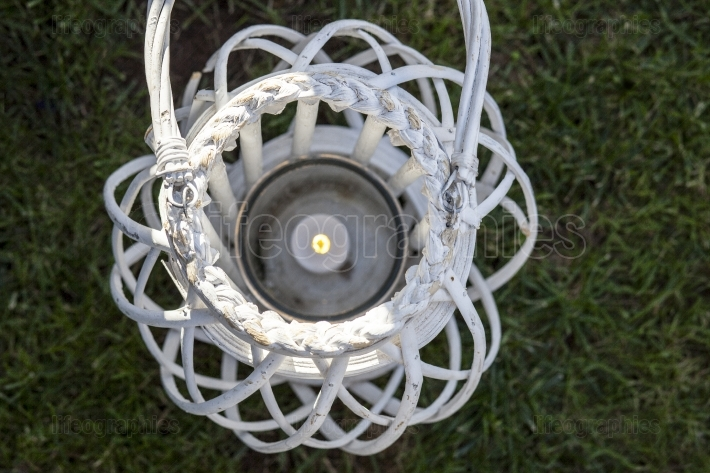 White wicker decorated lantern over green grass