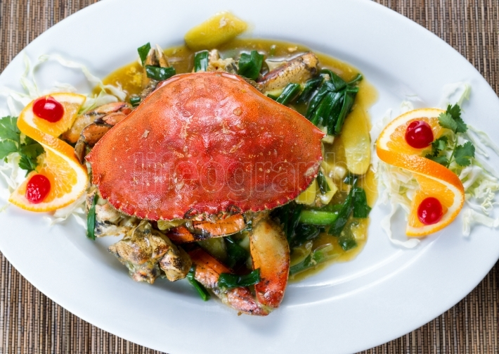 Whole cooked Dungeness crab with green onion sauce on white serv
