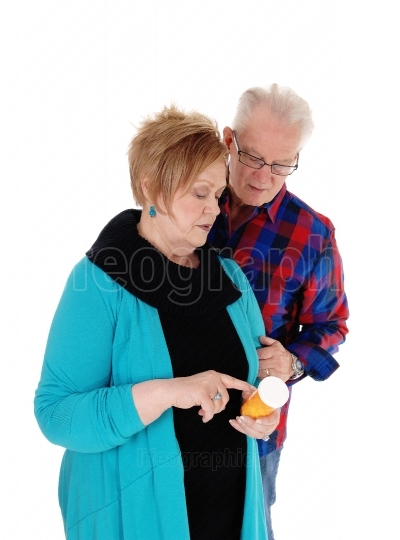 Wife showing husband his pills.