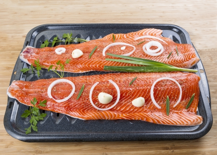 Wild Salmon Fillets and Herbs in Baking Pan on Wood Background