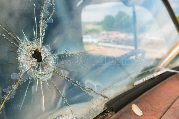 Windshield Of Junkyard Vehicle Has Hole And Cracks In Glass
