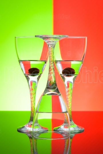 Wine glasses on glossy table surface and color background