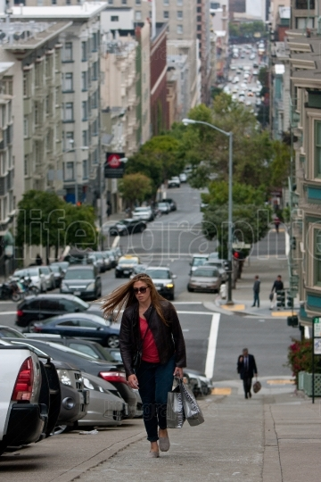 Woman carrying shopping bags climbs steep steps in nob hill