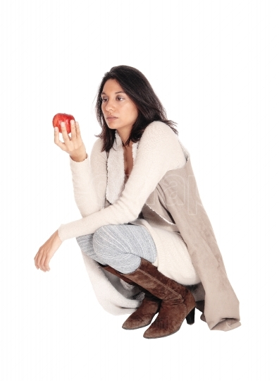 Woman crouching looking at a red apple