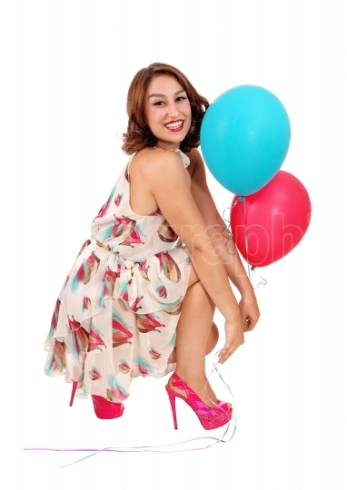 Woman crouching on floor with balloons.