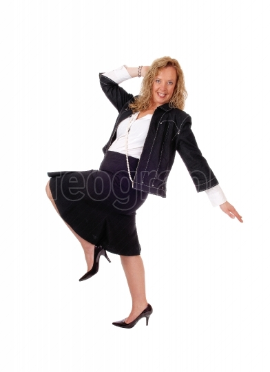 Woman dancing in skirt and jacket.