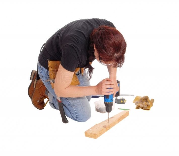 Woman drilling in wood.