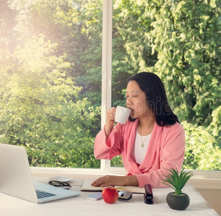 Woman enjoying her coffee in the morning light while working fro