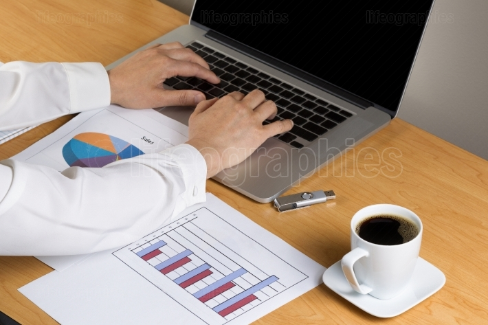 Woman hands typing on laptop keyboard while working on financial