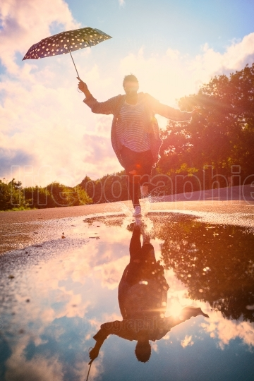 Woman having fun after rain, running in pond with her umbrella at sunset