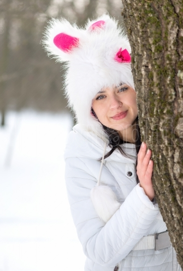 Woman hiding behind tree in winter season