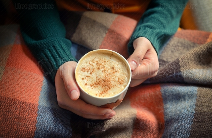 Woman holding hot cup of cappuccino