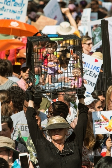Woman Holds Up Caged Dolls At Atlanta Immigration Law Protest