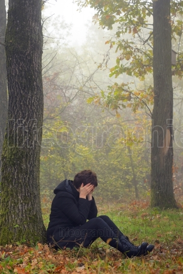 Woman in depression in forest feeling depressed