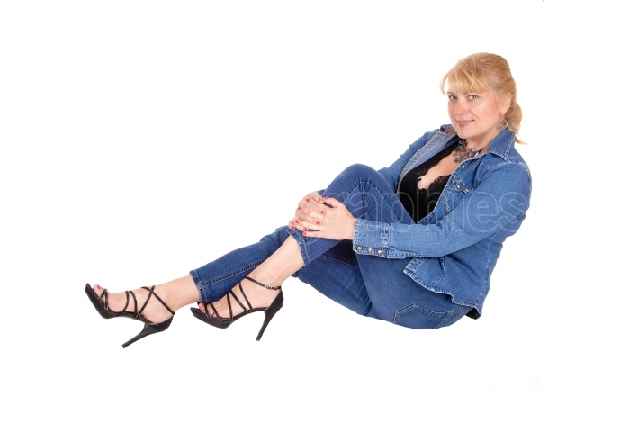Woman in jeans sitting on floor.