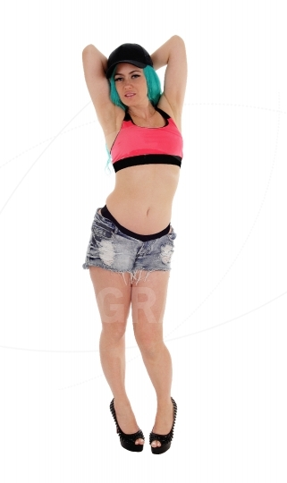 Woman in shorts with hands on head.