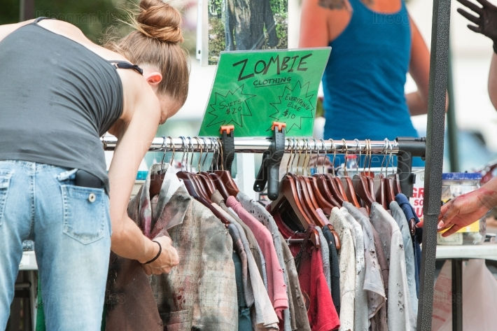 Woman inspects bloody zombie clothing before atlanta pub crawl