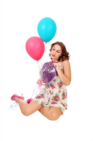 Woman kneeling on floor with balloons.